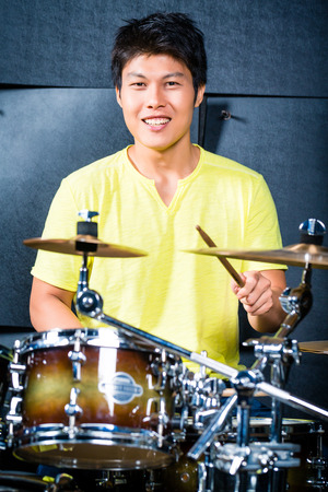 Asian professional musician drummer playing drums in recording studio