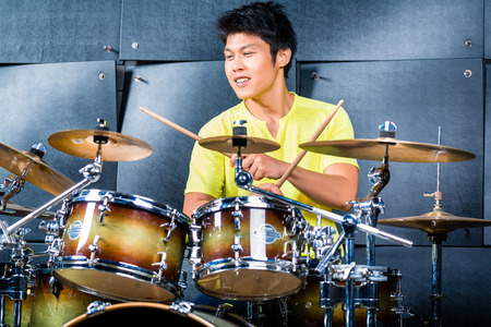 drumming: Asian professional musician drummer playing drums in recording studio