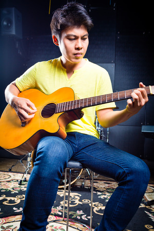 recording studio: Asian professional guitarist playing acoustic guitar music in recording studio