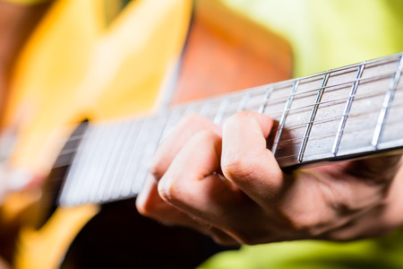 Asian professional guitarist playing acoustic guitar music in recording studio photo