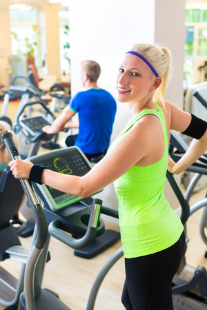 Group in gym on elliptical trainer photo