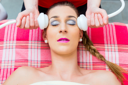 massager: Woman having relaxing herbal bag face massage in wellness spa Stock Photo