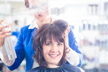 Female coiffeur giving women hairstyling with hairspray in hairdresser shop photo