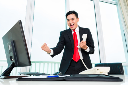 telephoning: Asian business man telephoning in office controlling profit