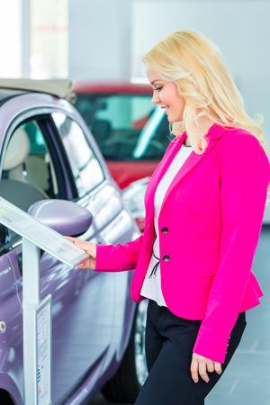 informing: Woman choosing car for buying in dealership