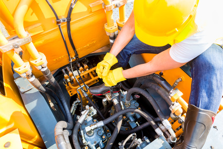 maintenance engineer: Asian motor mechanic working on construction or mining machinery in vehicle workshop