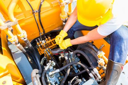 Mecânico de motor asiático que trabalha em construção ou mineração máquinas na oficina veículo