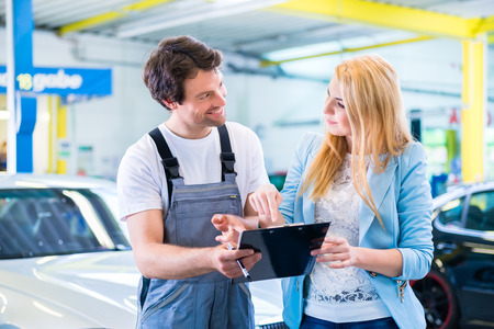 Male workshop mechanic handover car with checklist to client Stockfoto