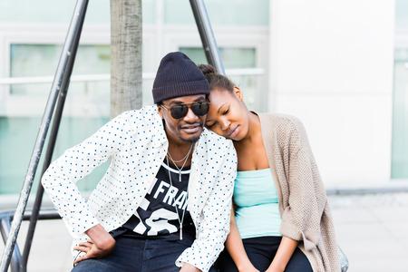 jovenes enamorados: Hombre africano sentado con su novia en la ciudad
