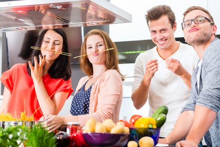 Friends cooking spaghetti and meat in domestic kitchen photo