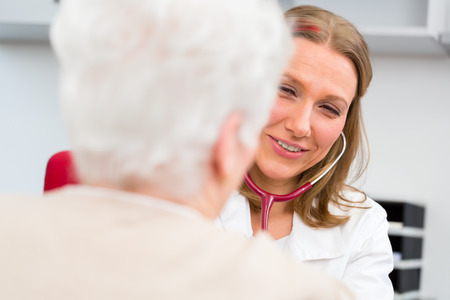 geriatric: Young female doctor measuring blood pressure of senior patient in surgery consultation hour