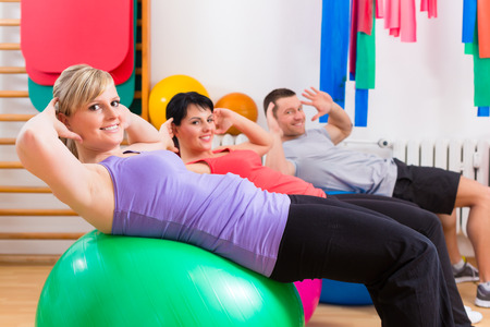 physical exercise: Patients at the physiotherapy doing physical exercises with therapist on training balls