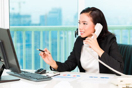 telephoning: Asian Chinese business woman telephoning in office controlling profit Stock Photo