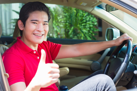 Asian man driving new car photo