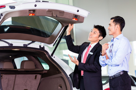 Car salesman in Asian dealership showing trunk of SUV car to customer Stock Photo