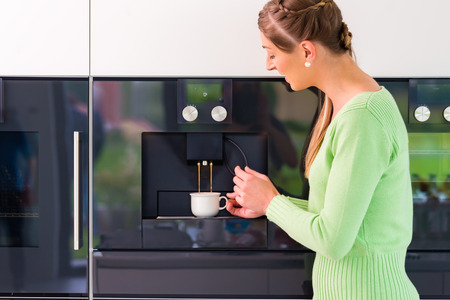 automatic machine: Woman using fully automatic coffee machine at home