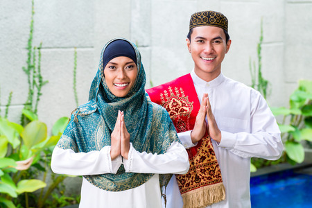 Asian Muslim man and woman welcoming guests wearing traditional dress photo