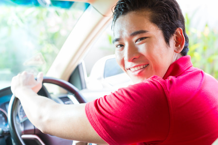 new driver: Asian man driving new car Stock Photo