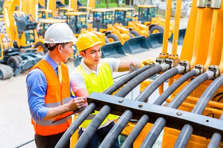 maquinaria pesada: Mecánico de motores de Asia discutir con lista de tareas ingeniero en el taller de máquinas de construcción Foto de archivo