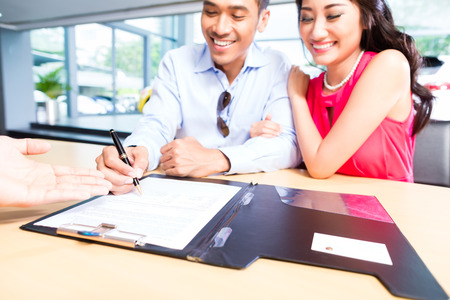 Asian Couple signing sales contract for car at dealership Archivio Fotografico