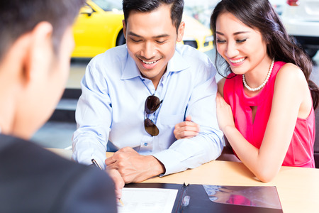 Asian Couple signing sales contract for car at dealership Foto de archivo