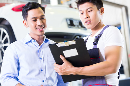 Asian Chinese car mechanic with customer going through the maintenance checklist photo