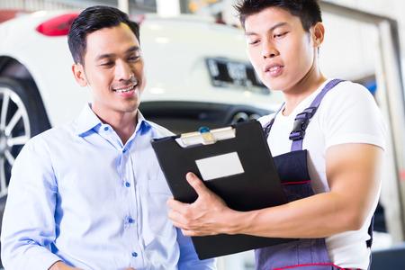 auto monteur: Aziatische Chinese automonteur met de klant gaan door het onderhoud checklist