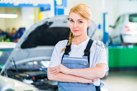 automobile workshop: Female auto mechanic working in car workshop