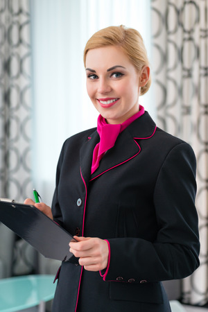 Housekeeping manager or assistant controlling hotel suit or suit with checklist on tidiness photo