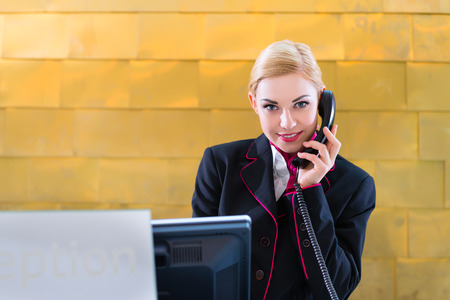 Hotel receptionist with phone on front desk photo