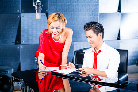 composer: Asian professional singer and pianist working and discussing on new song in studio for composing and recording Stock Photo