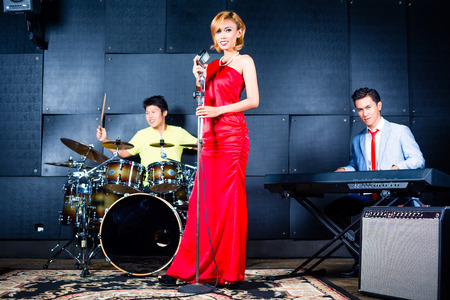 chinese drum: Asian professional singer drummer and keyboarder recording new song or album in studio