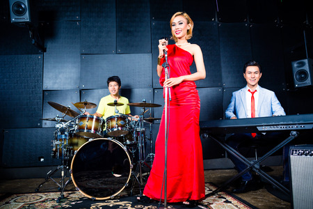 micro recording: Asian professional singer drummer and keyboarder recording new song or album in studio