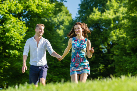 Couple in love running through park photo