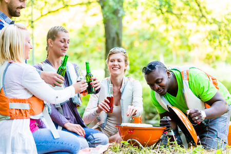 friends drinking: Friends barbecue in forest drinking beer Stock Photo
