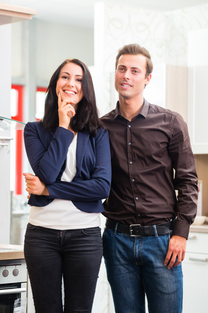 Man and woman buying domestic kitchen in studio or furniture store photo