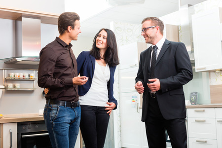 Man and woman consult salesman for domestic kitchen in studio or furniture store photo