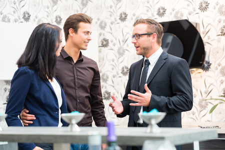 buys: Man and woman consulting salesman for domestic kitchen in studio or furniture store Stock Photo