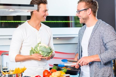 Friends cooking vegetables and meat in domestic kitchen photo