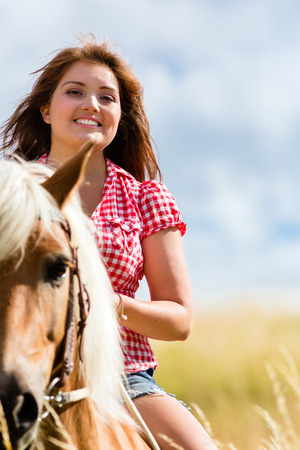Woman riding on horse in summer meadow photo
