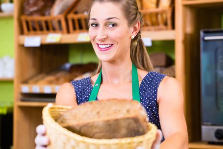 bakery store: Female baker at organic supermarket bakery offering customer bread Stock Photo