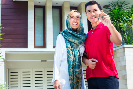 Asian Muslim man and woman moving into house presenting latchkey or key photo