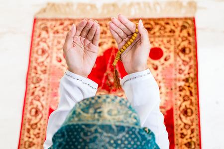 Asian Muslim woman praying on carpet with beads chain wearing traditional dress photo