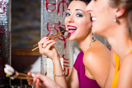 Young people eating sushi in Asia restaurant photo