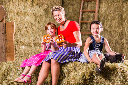hayloft: Bavarian mother and children sitting on hayloft with pretzels