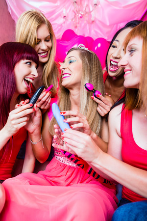 Women having bachelorette party with sex toys in night club photo