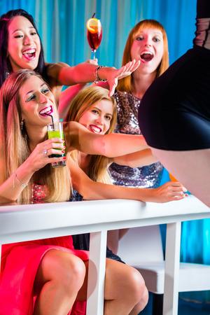 strip club: Friends watching striptease in strip club grabbing at female stripper