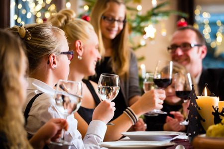 German parents and children toasting with wine and water at Christmas eve dinner