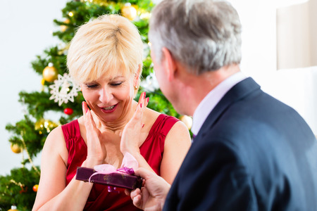 fulfil: Senior man giving gift to surprised woman on Christmas eve Stock Photo