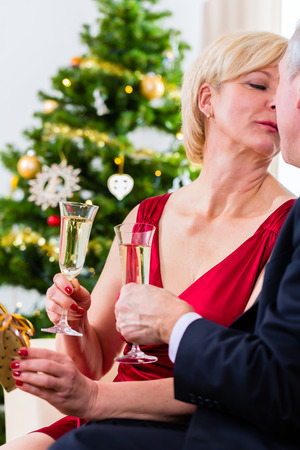 Senior man and woman celebrating Christmas eve with kiss and sparkling wine photo